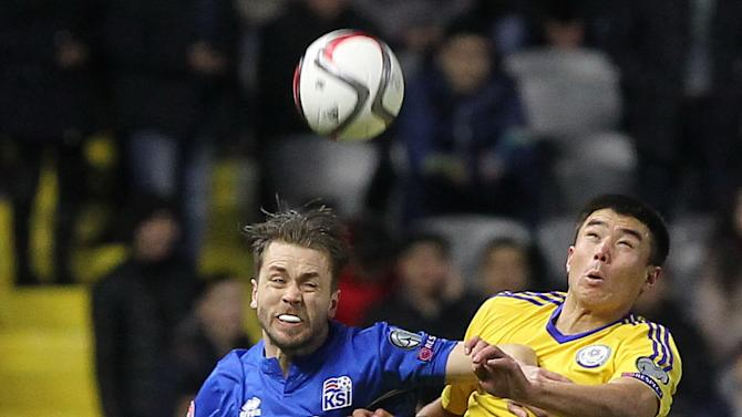 Iceland's Kari Arnason, left, and Kazakhstan's Daurenbek Tazhimbetov jump for a ball during the Euro 2016 qualifying soccer match between Kazakhstan and Iceland at Astana Arena stadium in Astana, the capital of Kazakhstan, Saturday, March 28, 2015. (AP Photo/Alexei Filippov)