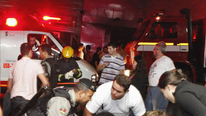 ALTERNATIVE CROP OF XSI103.- People help an injured man, victim of a fire in a club in Santa Maria city, Rio Grande do Sul state,  Brazil,  Sunday, Jan. 27,  2013.  According to police more than 200 died in the devastating nightclub fire in southern Brazil.  Officials say the fire broke out at the Kiss club in the city of Santa Maria while a band was performing. At least 200 people were also injured. (AP Photo/Agencia RBS)