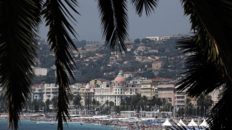 Tourists enjoy the sun on the beach during a sunny summer day in Nice
