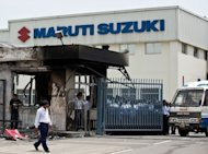 Indian private security guards stand behind the main gate of Maruti Suzuki Production Facility in Manesar, July 2012. India's largest passenger carmaker, Maruti Suzuki, reported a more than 40 percent slide in sales last month from a year earlier, as output at a key plant shaken by deadly violence tumbled