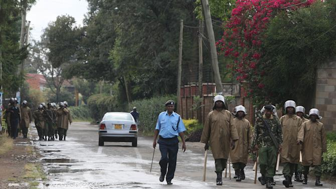Riot police patrol a street in Nairobi, Kenya Friday, March 8, 2013. The leading candidate in the race for Kenya's president is hovering around the 50 percent mark as ballots are counted on what officials say is the last day of the count.  The election commission said it expected to have final results by the end of Friday, though observers said it was still possible the count would go into the weekend. (AP Photo/Sayyid Azim)
