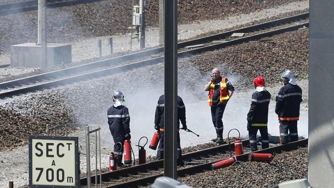 Firemen inspect the tracks after workers operating on the MyFerryLink car and passenger ferry boats set tires into fire at the entrance of the Eurotunnel Channel Tunnel linking Britain and France in Coquelles near Calais