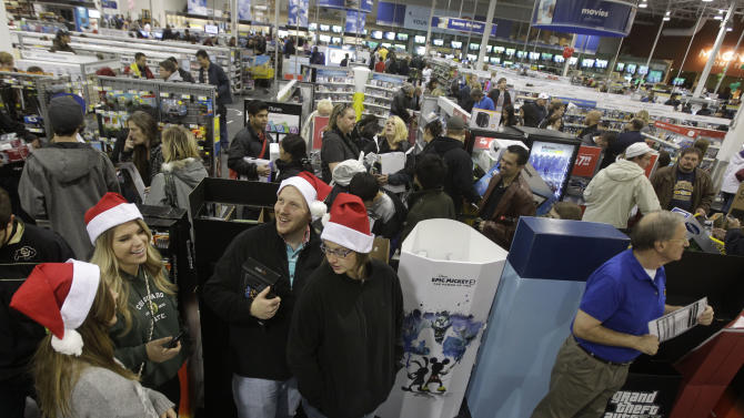 Shoppers, at bottom, right to left, Karin Carlson, of Wichita, Kan., her husband Jason, and her cousins Tylar Neu and Christie LaFever wait in line to pay for items for purchase at Best Buy electronics store, after doors opened for a Black Friday sale that started at midnight, in Broomfield, Colo., early Friday Nov. 23, 2012. (AP Photo/Brennan Linsley)