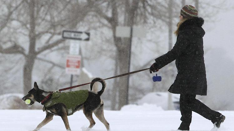 A woman walks her dog as a blizzard dropped snow over Boulder, Colo., Wednesday Dec. 19, 2012. A storm that has dumped more than a foot of snow in the Rocky Mountains is heading east and is forecast to bring the first major winter storm of the season to the central plains and Midwest. (AP Photo/Brennan Linsley)