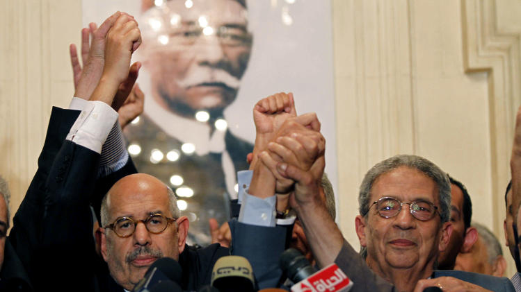 """FILE - In this Thursday, Nov. 22, 2012 file photo, former director of the U.N.'s nuclear agency and Nobel peace laureate, Mohamed El Baradei, left, and former Egyptian Foreign Minister and presidential candidate, Amr Moussa, raise their hands in solidarity after addressing a news conference flanked by other prominent politicians, not shown, from outside the Muslim Brotherhood, to decry what was interpreted as a de facto declaration of emergency law by Egyptian President Mohammed Morsi, in Cairo Egypt. Asked whether democracy was prevailing in his native Egypt, former Arab League Secretary-General Amr Moussa hedged, saying democracy """"is not only the ballot box. It is the respect of human rights, for rights of women, separation of powers, independence of the judiciary."""" (AP Photo/Mostafa El Shemy, File)"""