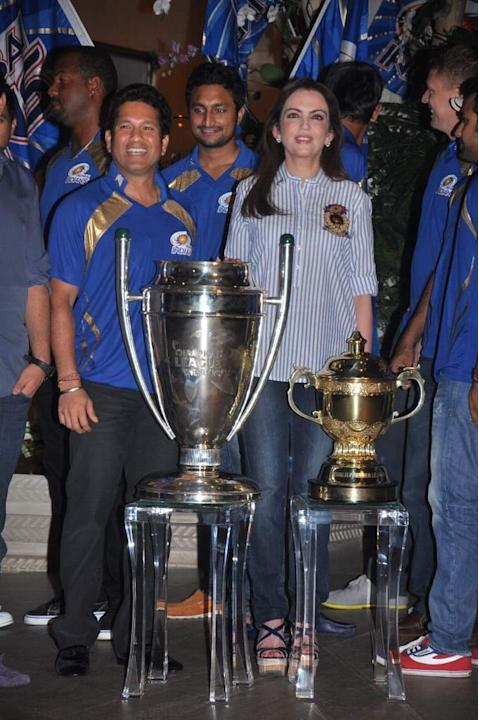 Sachin Tendulkar and Nita Ambani pose with the CLT20 and IPL trophies