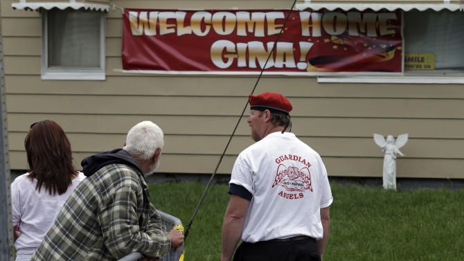 A member of the Guardian Angels stands watch outside the home of Gina DeJesus in Cleveland Friday, May 10, 2013. DeJesus was freed Monday from the home of Ariel Castro where she and two other women had been held captive for nearly a decade. (AP Photo/Mark Duncan)
