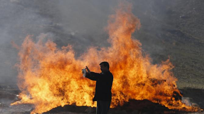 An Afghan police officer uses his mobile phone in front of a pile of burning illegal narcotics in the outskirts of Kabul