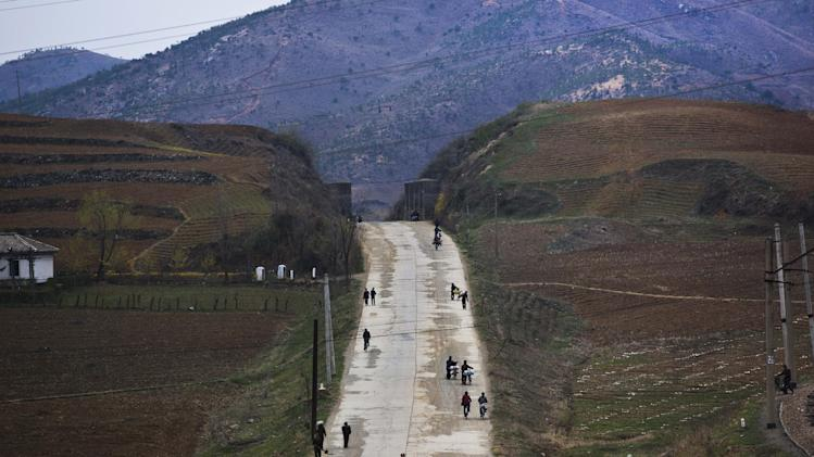 In this April 23, 2013 photo, North Koreans walk along a rural road north of Kaesong, North Korea. (AP Photo/David Guttenfelder)
