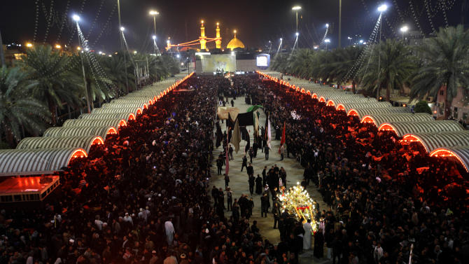 Shiite Muslim worshippers gather outside Imam Hussein shrine, seen in the background, to mark the Muslim festival of Ashoura, an important period of mourning for Shiites in Karbala, 50 miles (80 kilometers) south of Baghdad, Iraq, Saturday Nov. 24, 2012. The festival of Ashoura commemorates the martyrdom of Imam Hussein, the grandson of Prophet Muhammad at the Battle of Karbala, Iraq, in the year A.D. 680. (AP Photo/Khalid Mohammed)