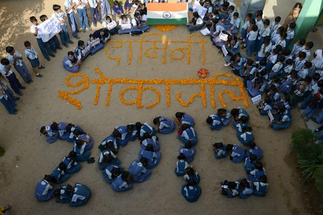 Indian school children pose for a photo as they pay homage to Delhi's rape victim as they welcome 2013 in Ahmedabad on December 31, 2012. Sydney will kick off a wave of dazzling firework displays welc