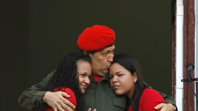 CORRECTS NAME OF DAUGHTER AT RIGHT -- Venezuela's President Hugo Chavez kisses his daughter Maria Gabriela, right, and embraces daughter Rosa Virginia after greeting supporters at a balcony of Miraflores presidential palace in Caracas, Venezuela, Monday, July 4, 2011. Chavez returned to Venezuela from Cuba on Monday morning, stepping off a plane hours before dawn and saying he is feeling better as he recovers from surgery that removed a cancerous tumor. (AP Photo/Ariana Cubillos)