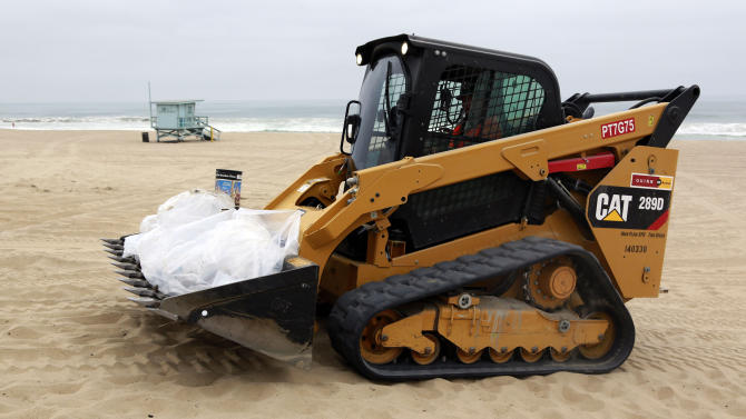 Contaminated bags of sand and oil are loaded onto a track loader in Manhattan Beach, Calif., on Thursday, May 28, 2015. Popular beaches along nearly 7 miles of Los Angeles-area coastline are off-limits to surfing and swimming after balls of tar washed ashore. The beaches along south Santa Monica Bay appeared virtually free of oil Thursday morning after an overnight cleanup, but officials aren't sure if more tar will show up. (AP Photo/Nick Ut)