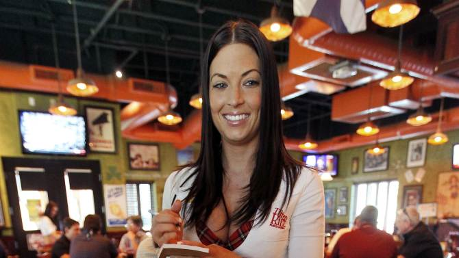 """In this May 16, 2012 photo, Ashley Carpenter takes lunch orders at the Tilted Kilt, in Tempe, Ariz. The Tilted Kilt is part of a booming niche in the beleaguered restaurant industry known as """"breastaurants,"""" or sports bars that feature scantily-clad waitresses. These small chains operate in the tradition of Hooters, which pioneered the concept in the 1980s but has struggled in recent years to stay fresh. (AP Photo/Matt York)"""