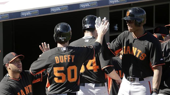 San Francisco Giants' Matt Duffy (50) celebrates coming into the dugout after scoring on a two-run double by Juan Perez during the fifth inning of a spring training baseball game against the Texas Rangers Friday, March 6, 2015, in Surprise, Ariz. (AP Photo/Charlie Riedel)