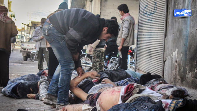 In this photo provided by the Syrian anti-government activist group Ariha Today, which has been authenticated based on its contents and other AP reporting, a Syrian man tries to identify victims after airstrikes believed to be carried out by Russian warplanes in the center of Ariha town in the northwestern province of Idlib, Syria, Sunday, Nov. 29, 2015. Syrian opposition media is reporting that airstrikes believed to be carried out by Russian warplanes have killed and wounded dozens of people in a northwestern Syrian market. (Ariha Today via AP)