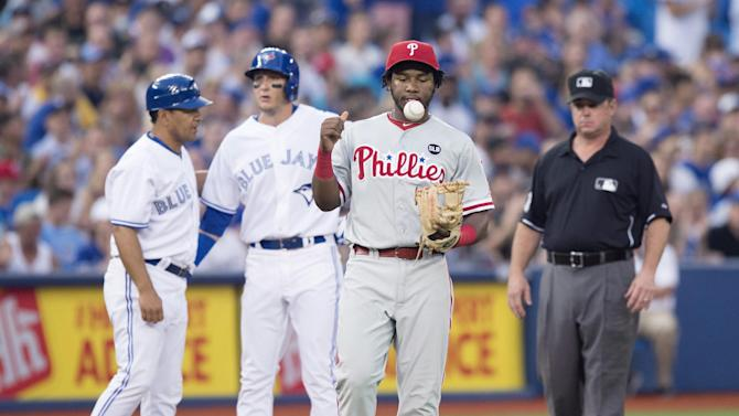 Philadelphia Phillies' Maikel Franco, second from right, tosses the ball as Toronto Blue Jays' Troy Tulowitzki stands on third base during fifth inning of a baseball game, Wednesday, July 29, 2015, in Toronto. (Darren Calabrese/The Canadian Press via AP) MANDATORY CREDIT