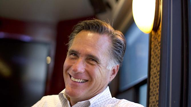 In this June 8, 2012, photo, Republican presidential candidate, former Massachusetts Gov. Mitt Romney smiles has he talks with his staff while riding on his bus after a campaign stop in Council Bluffs, Iowa. Republicans riding high from a string of breaks in their favor are increasingly optimistic about Romney's chances to claim the White House in November, even among conservatives who had qualms about making him the party's nominee. The bullish take is reflected in interviews with party strategists and activists, including people who supported Romney rivals during the primary season. Mood matters because it can fuel fundraising and volunteer hustle. But some of those GOP players stress that Romney has little room for error if he expects to topple an incumbent president. (AP Photo/Evan Vucci)