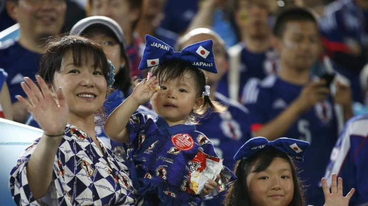 Fans of Japan's national soccer team wave ahead of their 2014 World Cup Group C soccer match against Greece at the Dunas arena in Natal