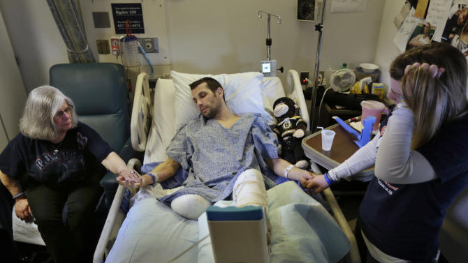 In this Thursday, May 9, 2013 photo, Marc Fucarile, center, holds hands with his mother, Maureen Fucarile, left, and his fiancee Jennifer Regan, right, in his room at Massachusetts General Hospital in Boston. Fucarile was only feet away from one of the bomb blasts Monday, April 15 near the finish line of the Boston Marathon that resulted in the loss of one leg, severe damage to the other, as well as burns, and a piece of shrapnel lodged in his heart. (AP Photo/Steven Senne)