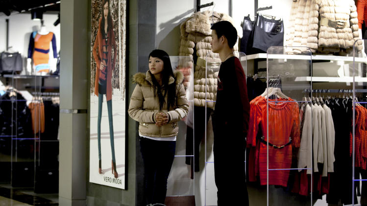 Employees wait for customers at a fashion boutique inside a shopping mall in Beijing Monday, Dec. 17, 2012. China's new Communist Party leaders are promising reforms aimed at reducing reliance on exports to drive growth and more spending if needed to prop up a shaky economic recovery. (AP Photo/Andy Wong)