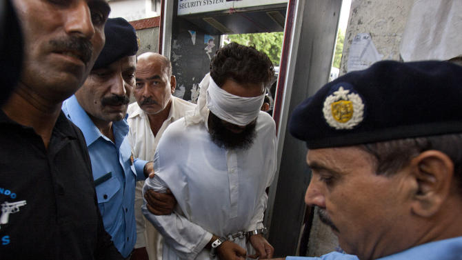 FILE - In this Sunday, Sept. 2, 2012, file photo, Pakistani police officers escort blindfolded Muslim cleric Khalid Chishti to appear in court in Islamabad, Pakistan. A lawyer says a Pakistani court has dismissed charges against the cleric who accused a young Christian girl of blasphemy and had been arrested for allegedly forging evidence against her. (AP Photo/Anjum Naveed, file)