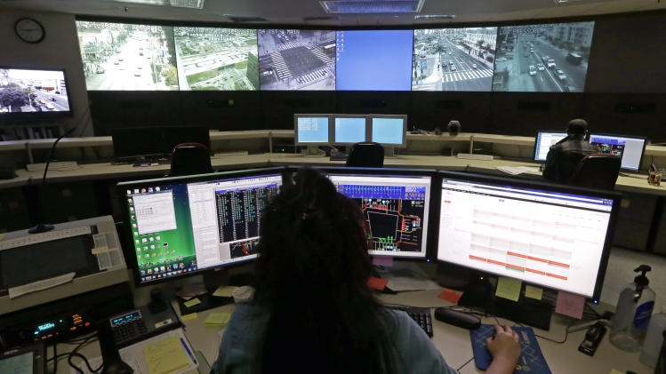 FILE - In this Wednesday, April 24, 2013 file photo transportation engineer associate Abeer Kliefe works at the Los Angeles Department of Transportation's Automated Traffic Surveillance and Control Center in downtown Los Angeles. In a 2011 poll by The Associated Press and the NORC Center for Public Affairs Research, 54 percent of those surveyed felt protecting citizens' rights and freedoms should be a higher priority for the government than keeping people safe from terrorists. At the same time, 64 percent said it was sometimes necessary to sacrifice some rights and freedoms to fight terrorism. (AP Photo/Reed Saxon, File)