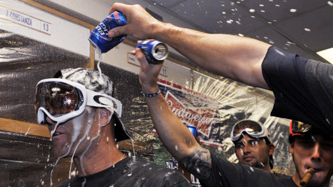 Atlanta Braves' Tim Hudson, left, celebrates with teammates after the Braves clinched the NL East title with a 5-2 win over the Chicago Cubs in a baseball game in Chicago, Sunday, Sept. 22, 2013. (AP Photo/David Banks, Pool)