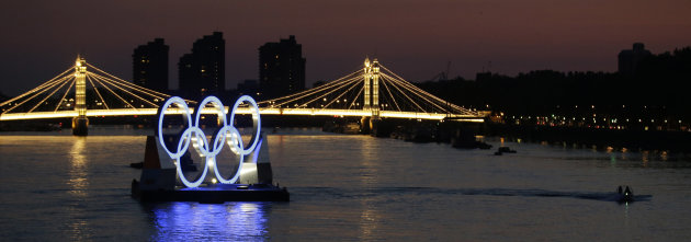 A boat passes a set of Olympic Rings floating in the River Thames off of Battersea park Tuesday, July 24, 2012, in London. The city will host the 2012 London Olympics with opening ceremonies scheduled for Friday, July 27. (AP Photo/Charlie Riedel)
