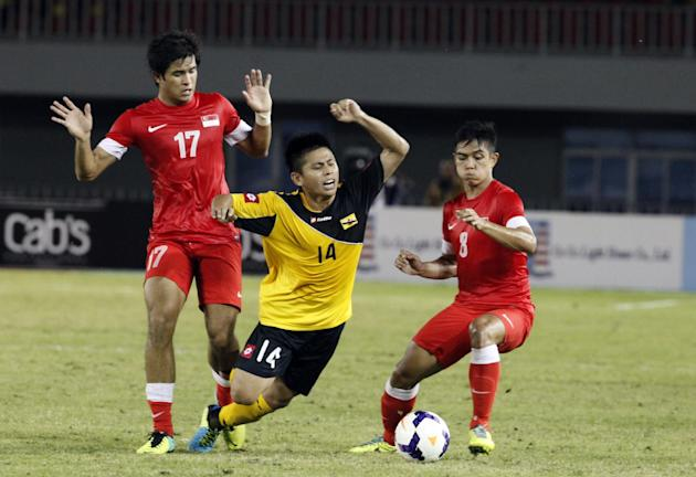Mohd Akmal Hakeen And Hamid of Brunei, center, falls as he vies for the ball against two Singapore players, Muhammad Hafis Abu Sujad, right, and Muhammad Zulfahmi Mohd Arifin, during their soccer matc