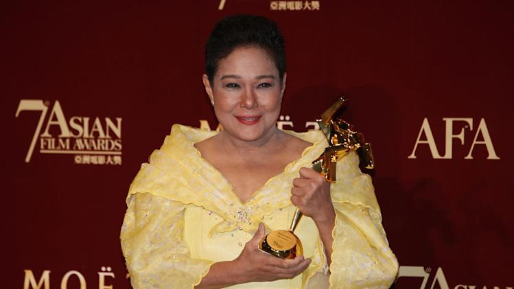 """FILE - In this March 18, 2013 file photo, Philippine actress Nora Aunor poses with her trophy after winning the Best Actress Award of her movie """"Thy Womb"""" at the Asian Film Awards as part of the 37th Hong Kong International Film Festival in Hong Kong. Philippine President Benigno Aquino III defended Tuesday, July 1, 2014 his decision not to appoint multi-awarded actress Aunor as national artist, saying doing so would send the wrong message that illegal drugs are acceptable. Aquino told reporters he decided to exclude the actress who rose from rags to stardom from this year's list of national artist appointees because of her previous drug conviction - a detail Aunor's lawyer says is wrong. (AP Photo/Kin Cheung, File)"""