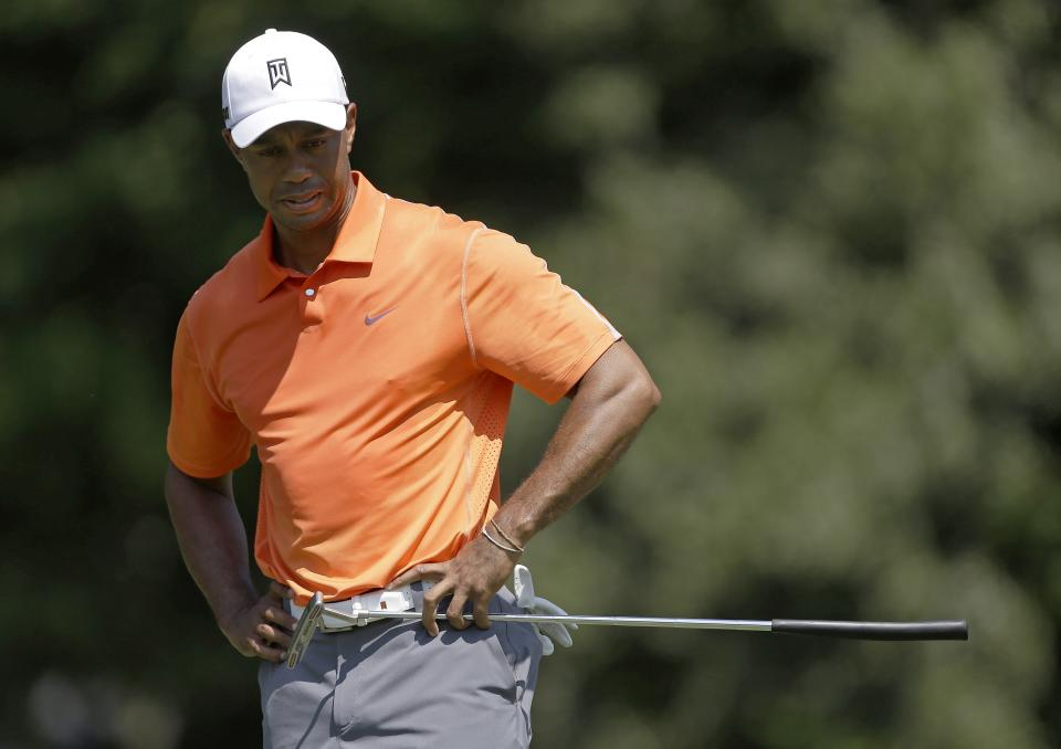 Tiger Woods looks over his putt on the second green during the first round of play in the PGA Tour Championship golf tournament at East Lake Golf Club in Atlanta, Thursday, Sept. 19, 2013. (AP Photo/John Bazemore)