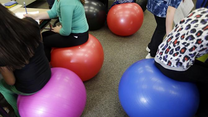 Students in Robbi Giuliano's fifth grade class sit on yoga balls as they complete their assignments at Westtown-Thornbury Elementary School Monday, Feb. 4, 2013, in West Chester, Pa.  By making the sitter work to stay balanced, the balls force muscle engagement and increased blood flow, leading to more alertness. (AP Photo/Matt Rourke)
