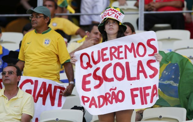 A protester holds a sign before the Confederations Cup Group A soccer match between Brazil and Mexico at the Estadio Castelao in Fortaleza