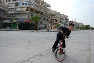 A Syrian child rides his bicycle along a deserted street in the Salaheddin district of the northern city of Aleppo. A temporary truce between warring parties in Syria has collapsed just hours after it began, with the army and rebels each accusing the other of violating the Muslim holiday four-day ceasefire
