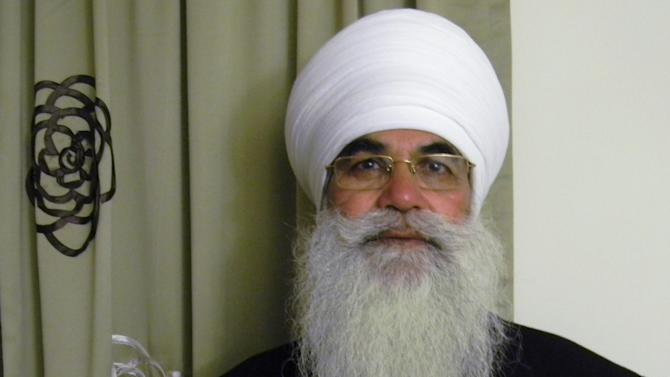 In this March 2012 photo provided by his family, Punjab Singh poses at a Sikh temple in Glen Rock, N.J. Singh was critically injured in a shooting rampage at a Sikh temple in Oak Creek, Wis., in August 2012 that left six people dead. The 65-year-old Sikh priest had remained largely unresponsive at a Wisconsin care facility until January 2013 when he began showing signs of cognitive improvement. (AP Photo/Family photo)
