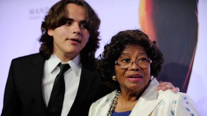 """FILE - In this June 29, 2013 file photo, Prince Jackson, left, and Katherine Jackson arrive at the world premiere of """"Michael Jackson ONE"""" at THEhotel at Mandalay Bay Resort and Casino in Las Vegas. The Jackson family matriarch tearfully testified in a Los Angeles courtroom on Friday, July 19, 2013, about her son, Michael Jackson's death and her concerns about the pace of his planned comeback concerts. She is suing concert promoter AEG Live LLC, claiming it failed to properly investigate the doctor who administered a fatal dose of anesthetic to her son in June 2009. (Photo by David Becker/Invision/AP, File)"""