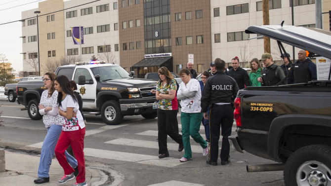Officers escort witnesses to a bus at the Renown Regional Medical Center after a lone gunman shot and injured four people before killing himself , Tuesday, Dec. 17, 2013 in Reno, Nev. (AP Photo/Scott Sady)