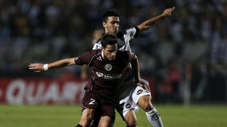 Melano of Argentina's Lanus fights for the ball with Barakat of Brazil's Ponte Preta during their Copa Sudamericana first leg final soccer match in Sao Paulo
