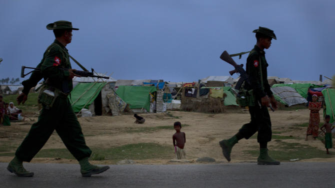 In this May 13, 2013 photo, an internally displaced Rohingya boy, center, watches army soldiers on foot-patrol in the foreground of makeshift tents at a camp for Rohingya people in Sittwe, northwestern Rakhine State, Myanmar. Authorities in Myanmar's western Rakhine state have imposed a two-child limit for Muslim Rohingya families, a policy that does not apply to Buddhists in the area and comes amid accusations of ethnic cleansing in the aftermath of sectarian violence. (AP Photo/Gemunu Amarasinghe)