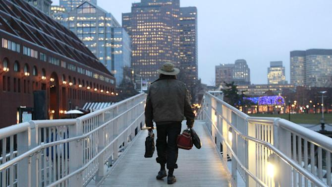 Michael Richard Smith carries a briefcase and a satchel as he walks up a gangway at a wharf in Boston Harbor, in Boston, Tuesday, Dec. 4, 2012. The 49-year-old Maine native said Tuesday that he's been paddling the waters of metro Boston since at least late summer with all of his possessions aboard a 14-foot, 40-year-old aluminum canoe that he patches with duct tape when necessary. (AP Photo/Steven Senne)