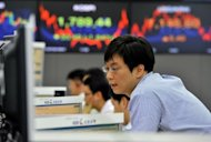 A currency dealer is seen monitoring exchange rates at the Korea Exchange Bank in Seoul, on July 23. S.Korea&#39;s economy grew more slowly than expected in April-June, central bank figures showed, as the eurozone debt crisis hit exports and consumption cooled down