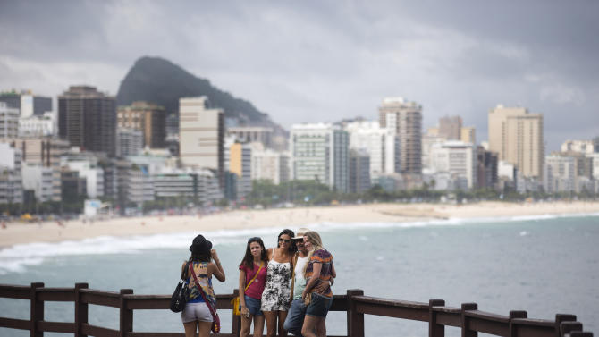 FILE -  In this May 9, 2014 file photo, tourists pose for a photo at the Leblon beach, in Rio de Janeiro, Brazil. Hundreds of thousands of foreign visitors are expected for the Olympics, which open Aug. 5. 2016. But there are growing concerns that some may stay away, frightened off by the mosquito-borne virus that is being linked to severe birth defects. (AP Photo/Hassan Ammar, File)