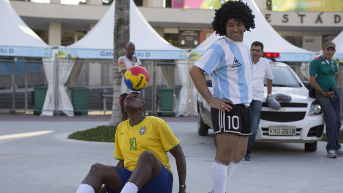 The street performing mime, Daniel Gonzalez, left, who is dressed to resemble Argentine soccer great Diego Armando Maradona, looks back at Marcio Pereira, dressed up as Brazilian soccer great Pele as he controlls the ball in front of Maracana stadium, Rio de Janeiro, Brazil, Wednesday, June 11, 2014. The World Cup soccer tournament starts Thursday. (AP Photo/Leo Correa)
