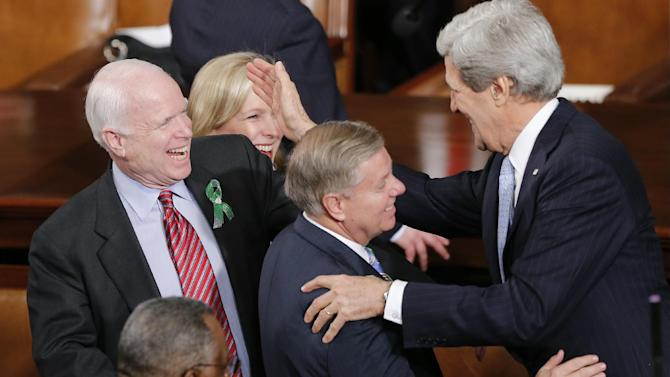 Secretary of State John Kerry, right, greets Sen.Lindsey Graham, R-S.C., center, and Sen. John McCain, R-Ariz, before President Barack Obama's State of the Union address during a joint session of Congress on Capitol Hill in Washington, Tuesday Feb. 12, 2013. (AP Photo/J. Scott Applewhite)