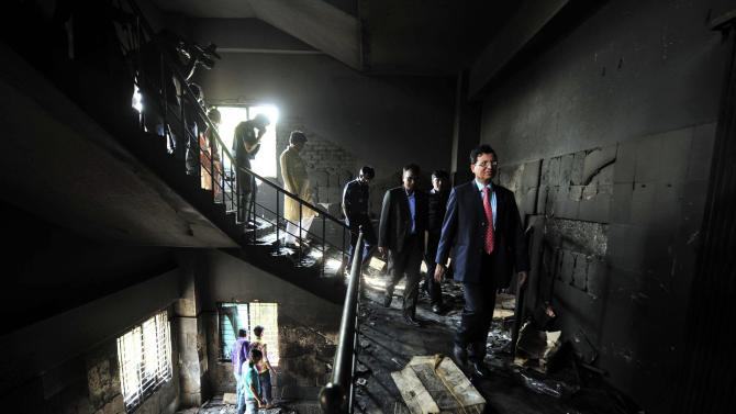 FILE - In this Monday, Nov. 26, 2012 file photo, Bangladeshi officials inspect a garment-factory where a fire killed more than 110 people Saturday  on the outskirts of Dhaka, Bangladesh. A Dhaka fire official said the Tazreen factory's fire safety certification had expired on June 30, and fire officials refused to renew it because the building did not have the proper safety arrangements. The factory did not have any fire exits for its 1,400 workers, many of whom became trapped by the blaze. Investigators said the death toll would have been far lower if there had been even a single emergency exit. (AP Photo)