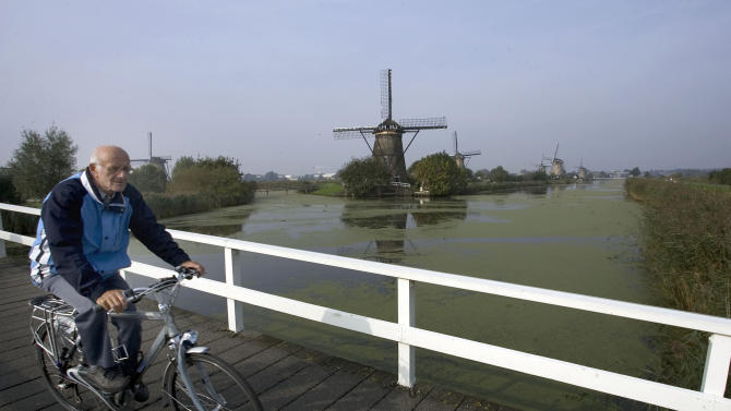 """FILE - In this Oct. 11, 2007 file photo a Dutch man rides his bike in front of windmills in Kinderdijk, Netherlands. While tax hikes and budget cuts have led to partisan warfare in the U.S. and widespread strikes in Southern Europe, in 2013 the Netherlands is weathering """"austerity"""" with relative grace. Some say that's because the country is experiencing a renaissance of its famed """"Polder Model,"""" a compromise system in which a centrist government works with labor unions and employers' associations to ensure the burden of painful economic reforms are shared across society. Poldering is deeply rooted in Dutch society: Historically the population had to cooperate to maintain a costly system of windmills and dikes to prevent floods and turn marshes into dry farmland known as polders. (AP Photo/ Evert-Jan Daniels, File)"""