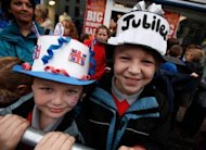 Children wearing homemade crowns await the arrival of Britain&#39;s Queen Elizabeth II at St Macartin&#39;s Church of Ireland Cathedral in Enniskillen, Northern Ireland. The queen shook hands with former IRA commander Martin McGuinness in a highly symbolic moment in the Northern Ireland peace process
