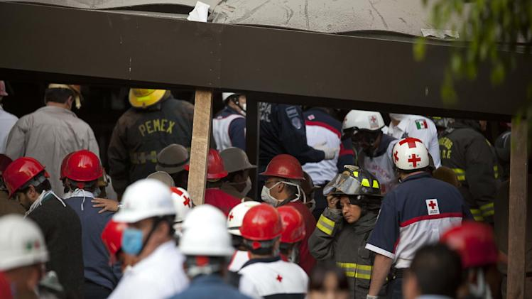 Rescue workers and firefighters gather at the site of an explosion at an adjacent building to the executive tower of Mexico's state-owned oil company PEMEX, in Mexico City, Thursday Jan. 31, 2013. An explosion at the main headquarters of Mexico's state-owned oil company in the capital killed more than 10 people and injured some 80 as it heavily damaged three floors of the building, sending hundreds into the streets and a large plume of smoke over the skyline. (AP Photo/Eduardo Verdugo)