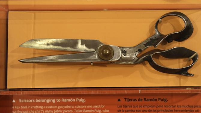 """In this Wednesday, Oct. 17, 2012 photo, sewing scissors that belonged to well-known guayabera tailor Ramon Puig are on display at an exhibition titled """"The Guayabera: A Shirt's Story"""" at the Museum of History Miami, in Miami. This is the first exhibition to trace the story of the shirt's evolution through Cuba, Mexico, and the United States. (AP Photo/Lynne Sladky)"""